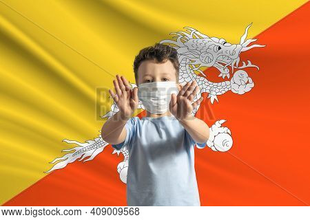Little White Boy In A Protective Mask On The Background Of The Flag Of Butane. Makes A Stop Sign Wit