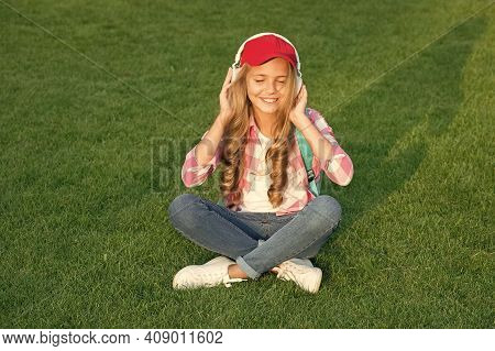 Listen Music While Relaxing Outdoors. Kid Girl Enjoy Music Green Grass Meadow. Pleasant Time. Child