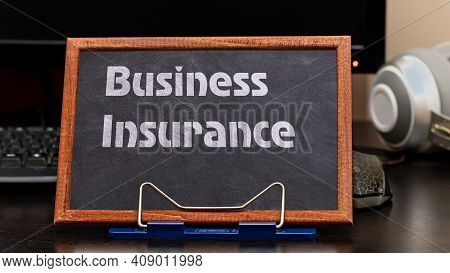 Business Insurance Services Concept. The Text Is Written On A Chalk Board Located At The Workplace N