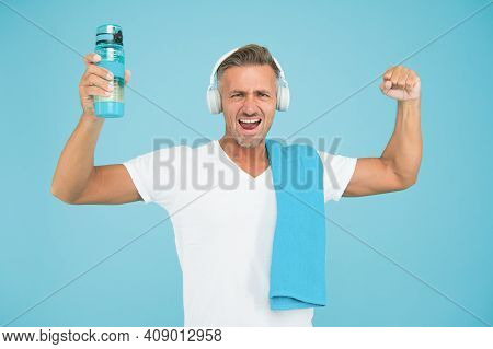 Staying Hydrated Staying Healthy. Healthy And Strong Man On Blue Background. Happy Athlete Celebrate
