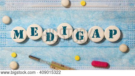Medigap, Text On White Paper On Blue Background. Medical Concept.