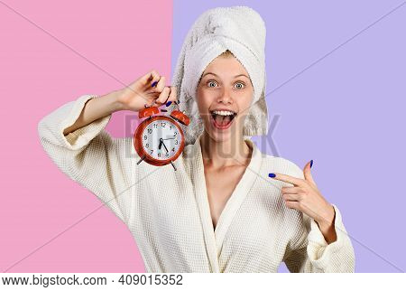 Smiling Morning Woman With Alarm Clock. Happy Girl In Bathrobe With Alarm Watch. Woman Pointing On A