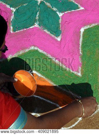 Indian Hindu  Woman Draw Rangoli During Harvest Festival Pongal Or Makar Sankranti
