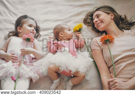 Portrait Of Three Girls With Flowers. A Sleeping Newborn Baby, A Little Girl And A Woman Lie On The