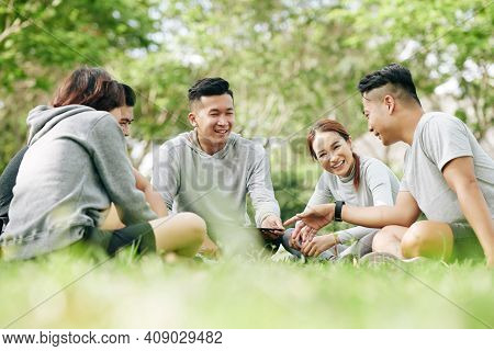 Group Of Joyful Young Students Sitting On Grass Loan On Campus And Discussing New Smartphone Model O