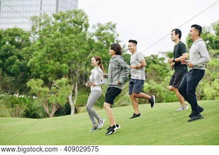 Group Og Young Vietnamese Sportsmen Running Down The Hill When Training In City Park