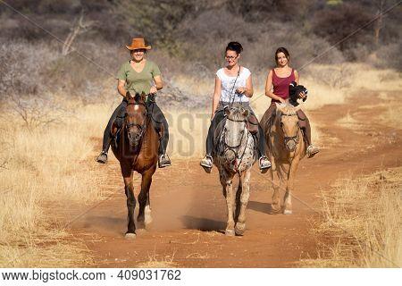 Three Women Ride Horses Along Dirt Track