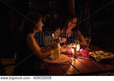 Two Women Drink Wine By Lantern Light