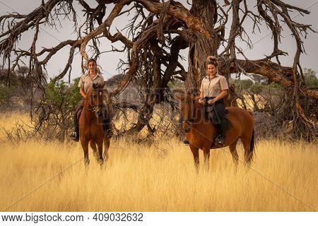 Two Women On Horseback Beside Dead Tree