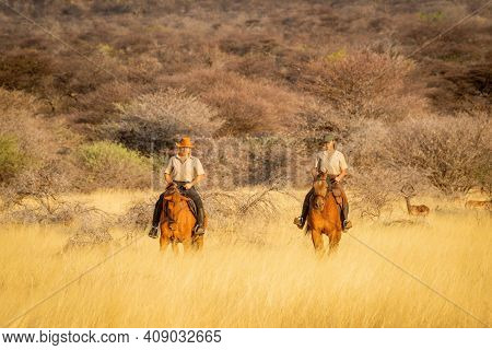 Two Women Ride Horses Watched By Impala