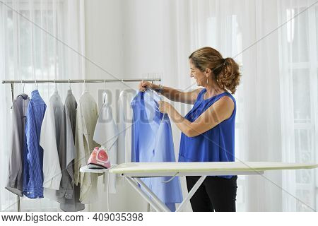 Smiling Pretty Mature Woman Hanging Shirts She Ironed On Hangers In Laundry Room