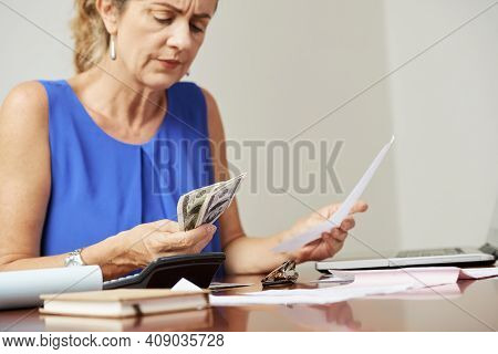 Frowning Stressed Mature Woman Counting Money She Needs To Pay For Mortgage And Utility Bills