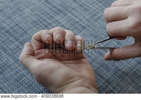 Adult Man Is Cutting His Own Hand Nails With Manicure Scissors. Hands Resting On A Blue Surface. Clo