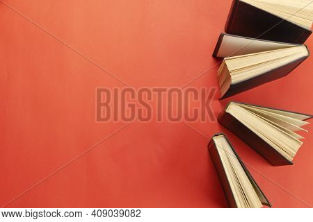 Сoncept Of Education, Knowledge, Wisdom. Group Of  Hardcover Books On A Red Table. Copy Space. Flat