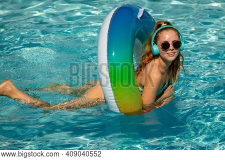 Summer Girl. Enjoying Suntan. Woman In Swimsuit On Inflatable Circle In The Swimming Pool