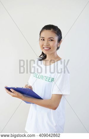 Portrait Of Pretty Smilng Young Asian Woman In Volunteer Shirt Filling Form For Project