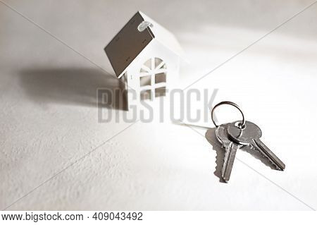 White Wooden House Symbol And Keys On A Gray Background. Cottage Construction Concept, Layout And De