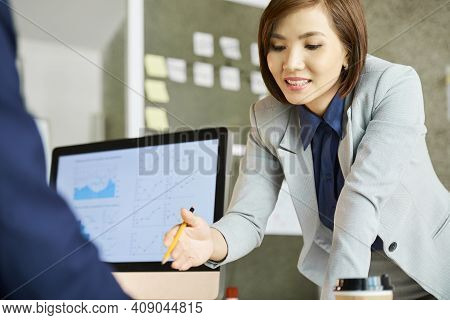 Beautiful Elegant Female Entrepreneur Leaning On Desk Of Her Colleague And Pointing At Document When