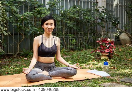 Happy Fit Young Asian Woman Sitting In Lotus Position On Yoga Mat In Backyard And Smiling At Camera
