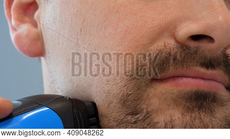 Male Hand Shaves Stubble With Electric Razor