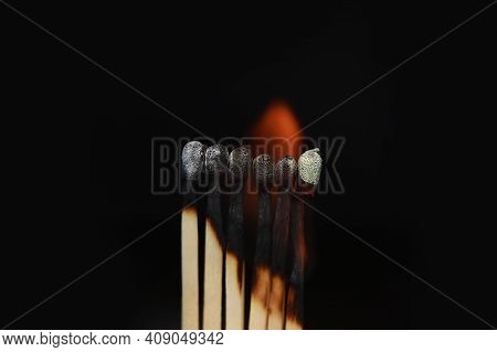 Burning Matches On Black Background. Matchsticks On Fire In Row Of Burning Is Sequence While One Mat