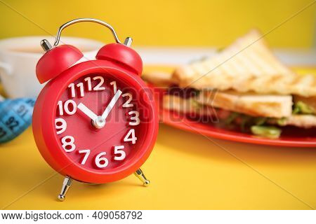 Alarm Clock On Yellow Background, Space For Text. Diet Regime
