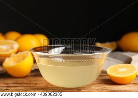 Freshly Squeezed Lemon Juice In Glass Bowl On Wooden Table