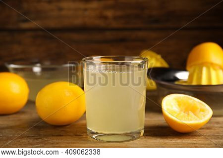 Freshly Squeezed Lemon Juice On Wooden Table