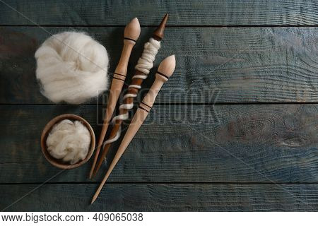 Soft White Wool And Spindles On Blue Wooden Table, Flat Lay. Space For Text
