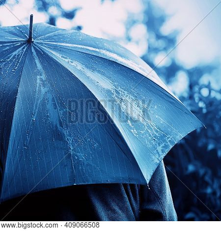 A Monochrome Image Of A Man In A Sweatshirt Under An Umbrella That Protects Him From The Cold Raindr