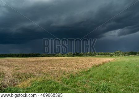 Dark Storm Clouds Over The Stubble And Meadow