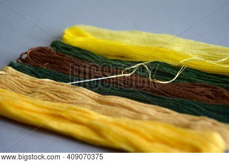 Needle With Thread And Set Of Multi-colored Cotton Threads On Gray Background. Colorful Mouline Thre