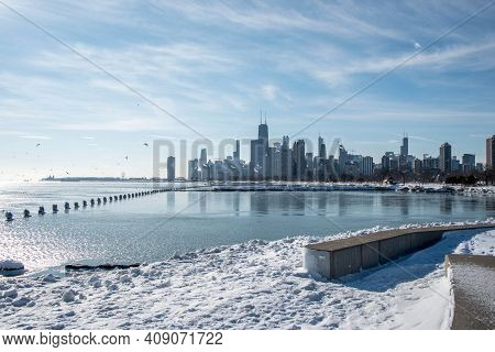 Chicago Skyline High Rise Buildings And Navy Pier As Seen Along The Shoreline Of Lake Michigan Under