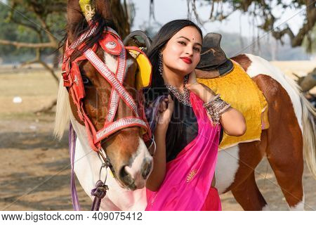 Outdoor Portrait Of Very Beautiful Indian Girl Wearing Saree And Holds The Reins Saddled Horse And P