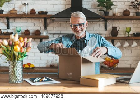 Happy Elderly Man Open A Parcel, Delivery Of Online Shopping To Home. A Satisfied Senior Customer.