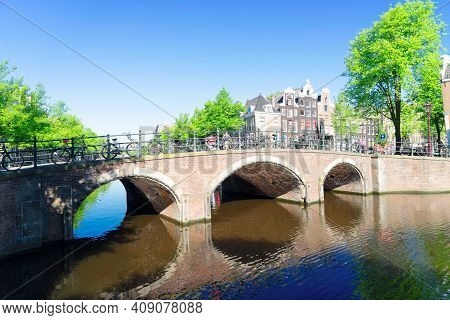 Bridge Of Amsterdam Over Canal Ring Famous Landmark In Old European Citye, Amsterdam Spring Scenery