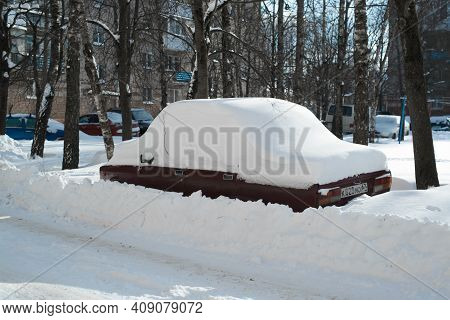 Car Under A Snowdrift On The Street. After Snowfall, Record Rainfall In Winter. Russia, Smolensk 02.