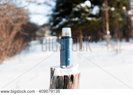 Camping Blue Thermos Standing On A Tree Stump In A Winter Sunny Forest. Travel, Camping Concept