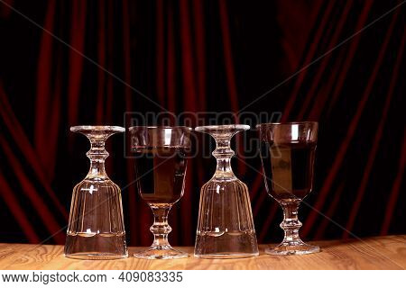Glasses Of Red Wine On The Background Of A Chic Red Velvet Fabric. The Concept Of A Romantic Dinner.
