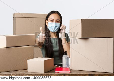 Small Business Owners, E-commerce And Covid-19 Preventing Virus Concept. Happy Asian Businesswoman I