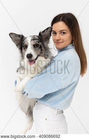 Happy Teenage Girl Holds Her Dog In Her Arms. Border Collie Dog. A Purebred Dog With A Proven Pedigr