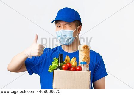 Online Shopping, Food Delivery And Covid-19 Pandemic Concept. Winking Cheerful Asian Male Courier In