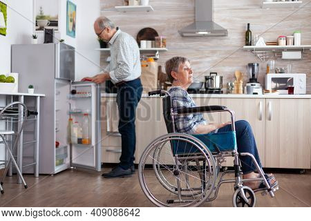 Handicapped Senior Woman In Wheelchair Sitting In Kitchen Looking Throug Window While Husband Unpack