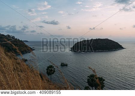Coast Of Phuket With Boats In Thailand At Dusk, With Golden Grass Peaking Up.