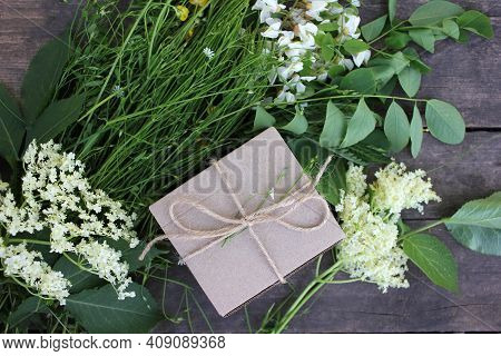 Brown Craft Gift Box Decorated With Natural Herbs And Flowers On Old Wooden Background With Copy Spa