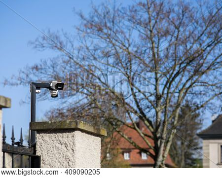 Cctv Camera On The Pole Surveilling The Area Behind The Large Cement Fence