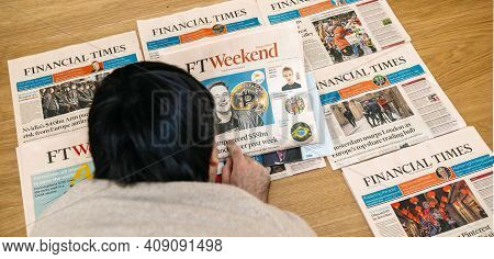 Paris, France - Feb 13, 2021: Overhead View Of Young Man Reading On The Wooden Floor Multiple Financ