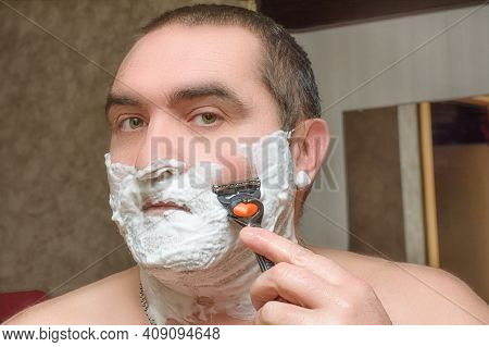 Man With Razor In Hand Shaves His Beard Stubble Covered With Shaving Foam. Male Facial Care Concept