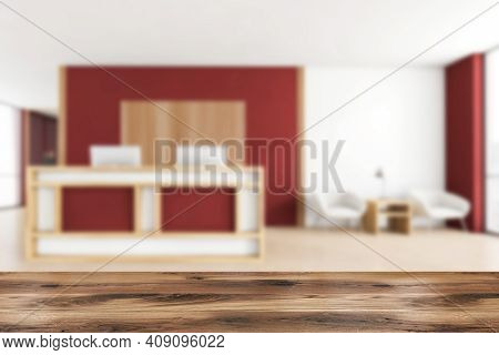 Wooden Desk Foreground On Blurred Background Of Red And Wooden Reception Room, Armchairs With Coffee