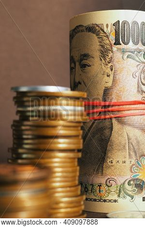 Japanese Money: Ten Thousand Yen Bills And Stacks Of Coins Close-up. Vertical Illustration On A Fina